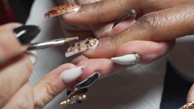 a nail artist working on a clients hands in a nail studio. - schönheitssalon stock-videos und b-roll-filmmaterial