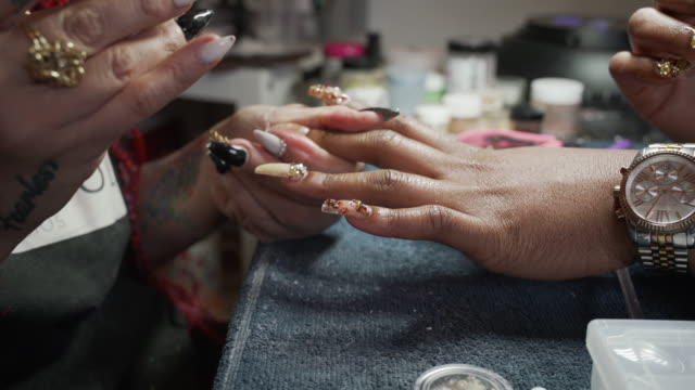 a nail artist working on a clients hands in a nail studio. - kunst, kultur und unterhaltung stock-videos und b-roll-filmmaterial