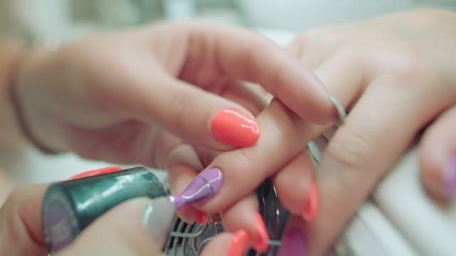 nail technician painting client's fingernails - technician stock videos and b-roll footage