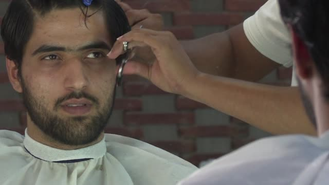 Nails are buffed and beards trimmed to the sound of clipping scissors inside the Men's salon in Pakistan's capital Islamabad where a growing number...