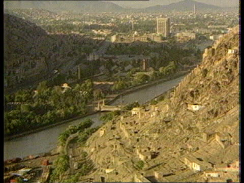 kabul tgv houses on hillside and river tilt up more of kabul with mountains in b/g afghan soldier indicating to car to stop and starts to check it bv... - カブール点の映像素材/bロール