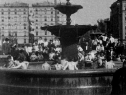 vídeos de stock e filmes b-roll de b/w 1903 naked boys jumping into fountain + are chased out by irate men / nyc / newsreel - 1903