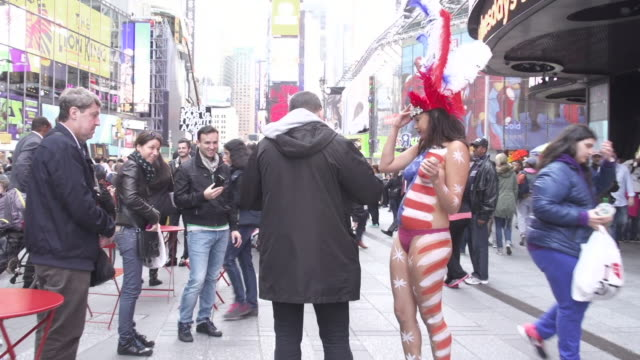Naked girl painted with American flag image posing with tourists for tips on Times Square in New York City NO
