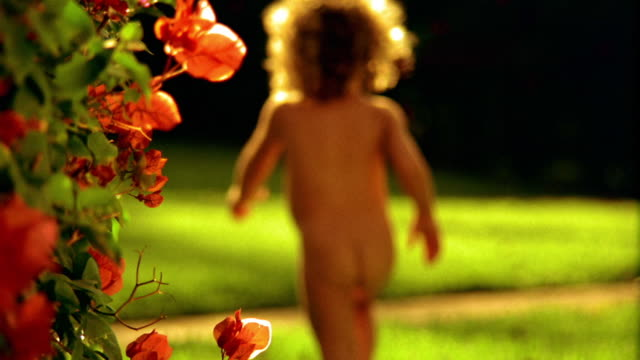 SOFT FOCUS REAR VIEW naked girl toddler running away from camera outdoors / Hawaii