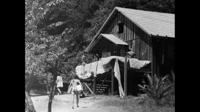 naked male hippie carries items in rural commune; 1967 - fkk stock-videos und b-roll-filmmaterial