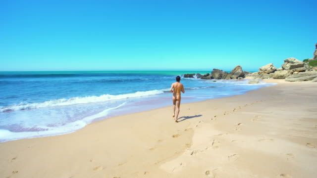 naked man (from behind) alone in an amazing and unspoiled beach in the spain coast - naked stock videos and b-roll footage