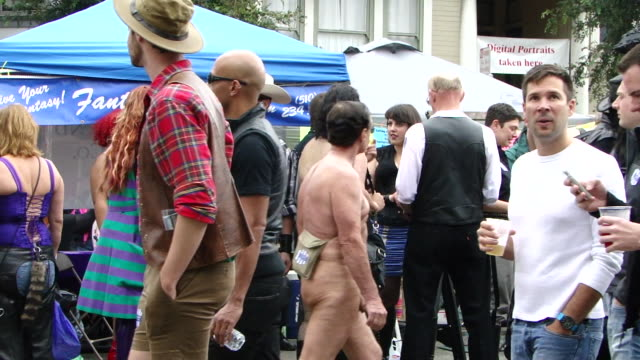 """naked people, people in costumes, and people in regular clothes walking across camera; booths in the background """"fetisch ..."""", """"paddle daddy"""",... - fetischismus stock-videos und b-roll-filmmaterial"""