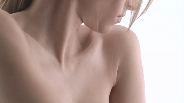 cu, naked woman caressing her bust in studio - junge frau allein stock-videos und b-roll-filmmaterial