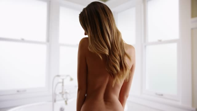vídeos y material grabado en eventos de stock de naked young caucasian woman shown from behind standing in bathroom or spa - articulación humana