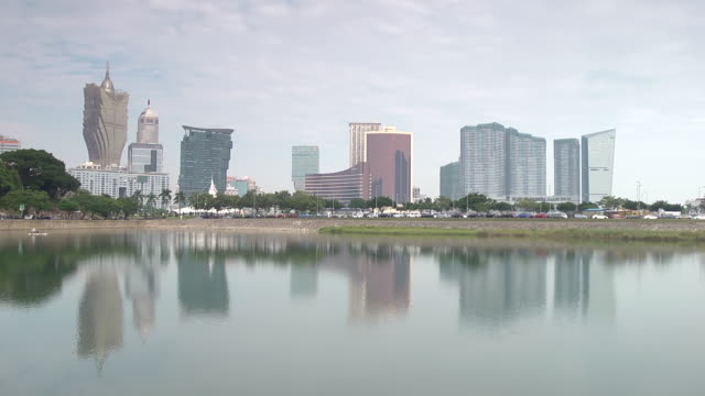 nam van lake, skyline w/ hotels, casinos, grand lisboa, wynn macau, mandarin oriental macao, resorts reflecting in water. casinos, gambling, gaming,... - macao stock videos & royalty-free footage
