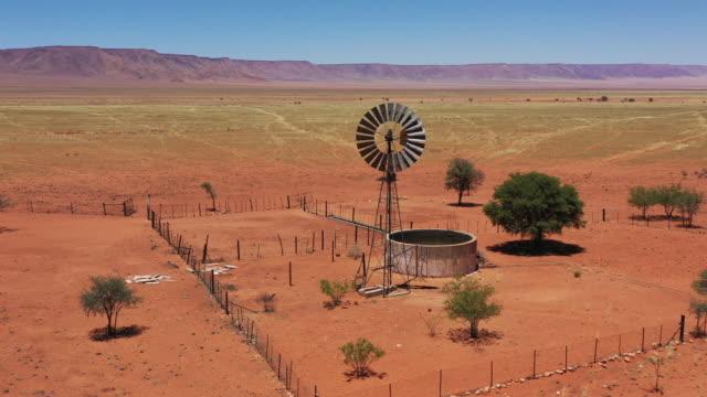 vídeos de stock, filmes e b-roll de namíbia rural agricultura gerador de eletricidade de turbina eólica em waterhole 4k vídeo - deserto de kalahari