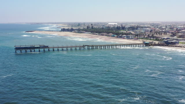namibia swakopmund beach and jetty 4k video drone flight - namibia stock videos & royalty-free footage