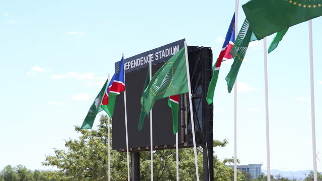 namibian flags and african union flags stand against the blue sky during the celebration of the 29th anniversary of liberation of the country, at the... - 映像技法点の映像素材/bロール