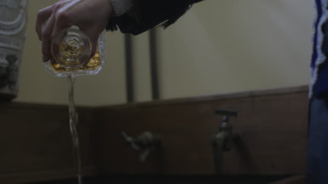 cu slo mo tu nancy astor pouring alcohol out of decanter into sink / edinburgh, scotland, united kingdom - decanter stock videos & royalty-free footage