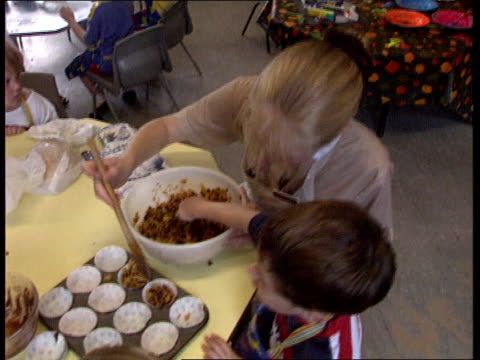 nannies register proposed; lib ???: norland nannies in nursery with children making cornflake cakes - cereal plant stock-videos und b-roll-filmmaterial