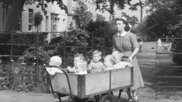 1950 ts nanny pushing cart carrying toddlers through the gate, rounding the corner, and down the lane at group home facility / united kingdom - foster care stock videos & royalty-free footage