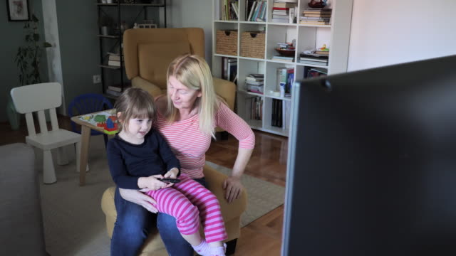 nanny watching tv at home with 3 year old girl - family with one child stock videos & royalty-free footage