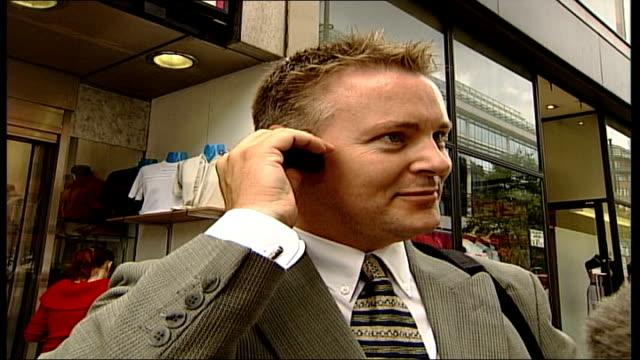 napster makes legal comeback; itn england: london: ext member of public looking at mp3 machine and putting it to his ear sot - it goes something like... - mp3 player stock videos & royalty-free footage
