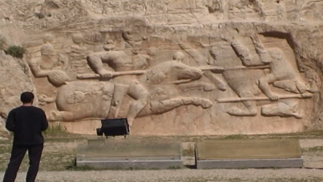 naqsh-e rustam. view of iranian tourists in front of the equestrian relief of hormizd ii depicting the sasanid kin forcing an enemy from his horse,... - felswand stock-videos und b-roll-filmmaterial