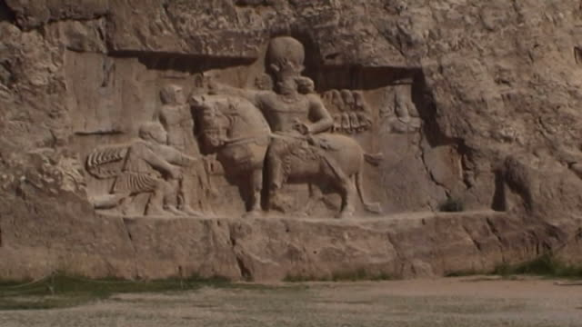 naqsh-e rustam. view of the sassanid rock-relief known as the triumph of shapur i depicting the victory of shapur i over two roman emperors, valerian... - felswand stock-videos und b-roll-filmmaterial