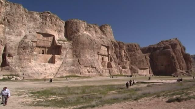 naqshe rustam wide of the achaemenid and sasanian necropolis showing the rockcut tombs of artaxerxes i darius i and xerxes i - parete rocciosa video stock e b–roll