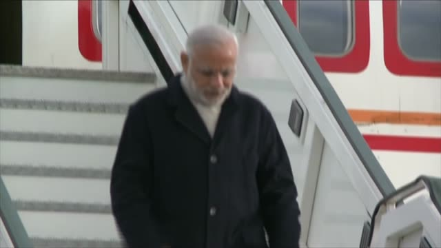 stockvideo's en b-roll-footage met narendra modi arrives at heathrow england london heathrow airport ext air india plane taxis on tarmac / narendra modi emerges from plane door puts... - parlementslid