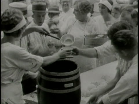 vídeos de stock, filmes e b-roll de narrated / 1933 newsreel / at a tent city, women dish up soup for earthquake survivors / group of women clean dishes at an outdoor table / people... - narrating