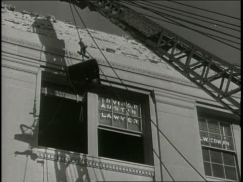 vídeos de stock, filmes e b-roll de narrated / 1933 newsreel / business owners carry items out of their stores / construction equipment aids in the removal of an office chair through a... - narrating