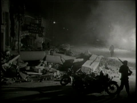 vídeos de stock, filmes e b-roll de narrated / 1933 newsreel /officers patrol the streets at night, with their guns on the shoulders /men patrolling streets among the rubble of... - narrating