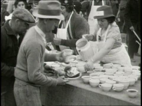 narrated / 1933 newsreel / survivors of the earthquake line up for food in tent city / volunteers help dress a young girl in warmer clothes / men... - plucking an instrument stock videos and b-roll footage