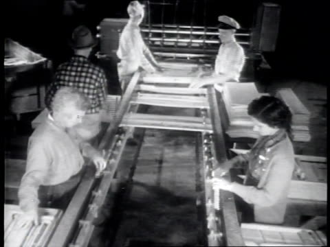 narrated / a machine spinning / sheets of wood come down a slide as workers guide and monitor the wood / a machine strips logs into long sheets of... - wood material stock videos & royalty-free footage
