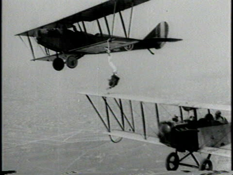 vídeos de stock e filmes b-roll de narrated / a pilot and another man checks sturdiness of hook on plan wing / in front of biplane man puts black hood over al johnson's head while... - durabilidade