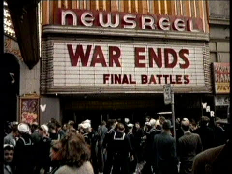 vídeos y material grabado en eventos de stock de narrated / a woman tears rationing stamps / a movie theater's marquee says war ends / a group of people cheer as they run alongside a streetcar / the... - narrar