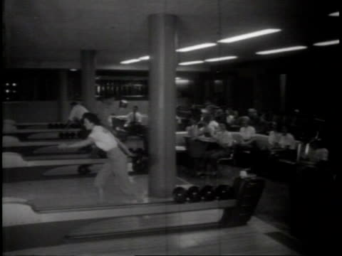 narrated / a worker adjusts a machine / a woman bowls in the recreation facility / employees sit and eat near the bowling alleys / a man pays for his... - ボーリング場点の映像素材/bロール