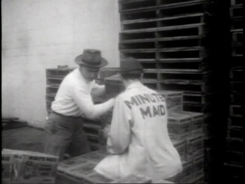 narrated / a worker drives pallet truck of boxes around the loading dock beside train / workers in minute maid uniforms and hats pull boxes of minute... - c119gs点の映像素材/bロール