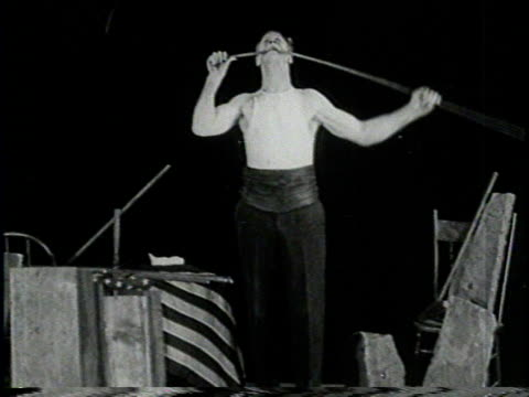 narrated / al ritchie bends a metal bar by holding one end in his mouth and twisting the other end with his hand smiles to camera / next he places a... - stunt person stock videos & royalty-free footage