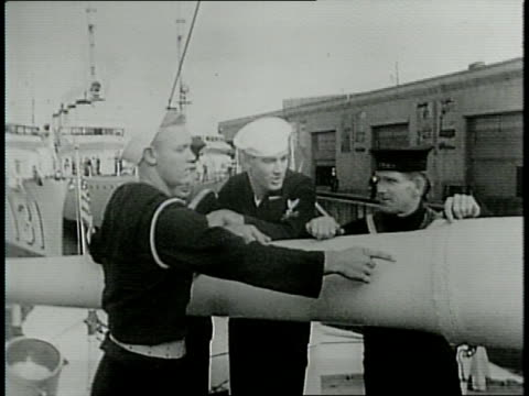 narrated / american sailors teaching british sailors about how their guns function / american and british sailors pal around and smoke cigarettes... - narrating stock videos & royalty-free footage