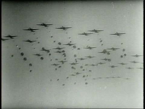 Narrated / American soldiers in battle advance / Squadron of American war planes in air / Bombs drop from American bomber planes and bombs explode on...