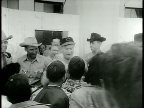 narrated / bob hope gets rub down by cleveland indians / hope signs autographs flanked by men in cowboy hats / - カウボーイハット点の映像素材/bロール