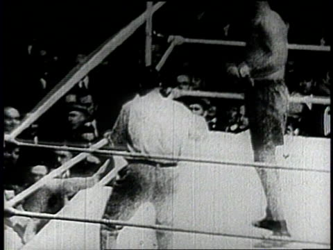 vídeos de stock, filmes e b-roll de narrated / boxing match between jack dempsey and luis firpo / dempsey knocks out firpo in the second round after knocking him down eight times - narrating