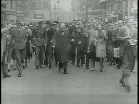 Narrated / Churchill walks down city street flanked by guards and his cabinet to inspect damage / shot of fires being extinguished / rubble / from...