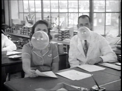 Narrated / Exterior of Fleer's Gum production facility / Researchers blow and sustain bubbles in an office / A woman blows a bubble and a researcher...