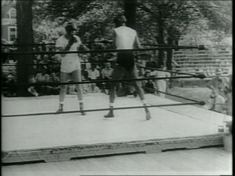 narrated / joe louis at training camp in pompton lakes, nj / spectators watch him sparring in practice ring / trainer throwing a medicine ball at him... - narrating stock videos & royalty-free footage