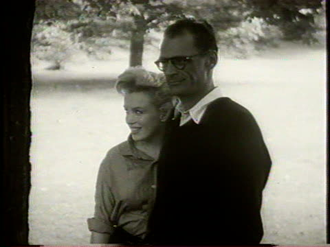 stockvideo's en b-roll-footage met narrated / marilyn monroe and her new husband arthur miller pose for photographers in their backyard / - marilyn monroe