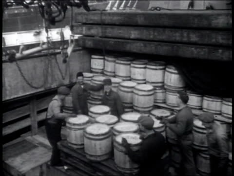 Narrated / Men unload barrels one by one from the pallet onto the ship deck / jeeps are lifted in the air by crane and onto the ship deck /