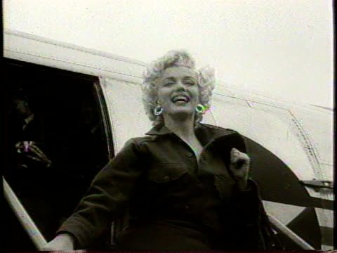 stockvideo's en b-roll-footage met narrated / newsreel / marilyn exits a plane wearing gi wear and boots and waves to the crowd as cameras flash / gi's run over to see marilyn / she is... - marilyn monroe