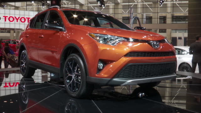 narrator introducing rav4 revolving on turntable / slogan on turntable base; ped up - front end of rav4 / headlight; front end / wheel / xcu tail... - narrating stock videos & royalty-free footage