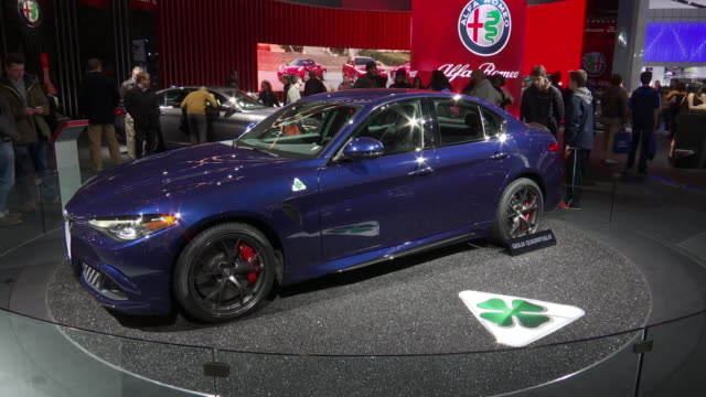 ws narrator introducing the car revolving on turntable / ws front quarter driver side of blue giulia / cu alfa sign zo ws passenger side profile of... - narrating stock videos and b-roll footage