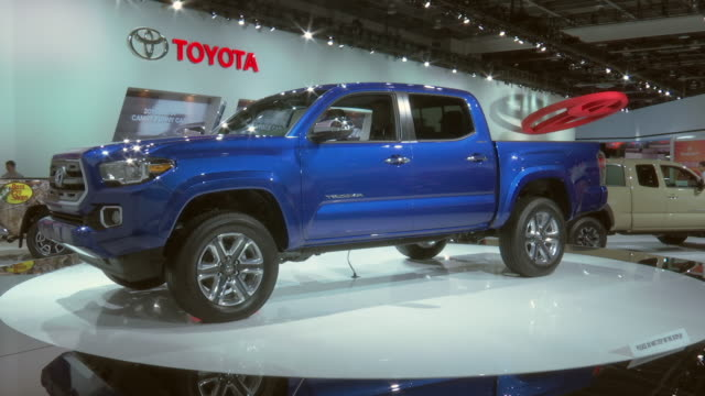 stockvideo's en b-roll-footage met ws narrator talks with truck on turntable behind him / ws toyota wall sign zo ws truck revolving on turntable / cu front end / zo ws front end / cu... - toyota motor