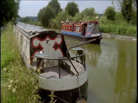 vídeos de stock e filmes b-roll de narrow boat passes moored vessel on canal uk - barco casa